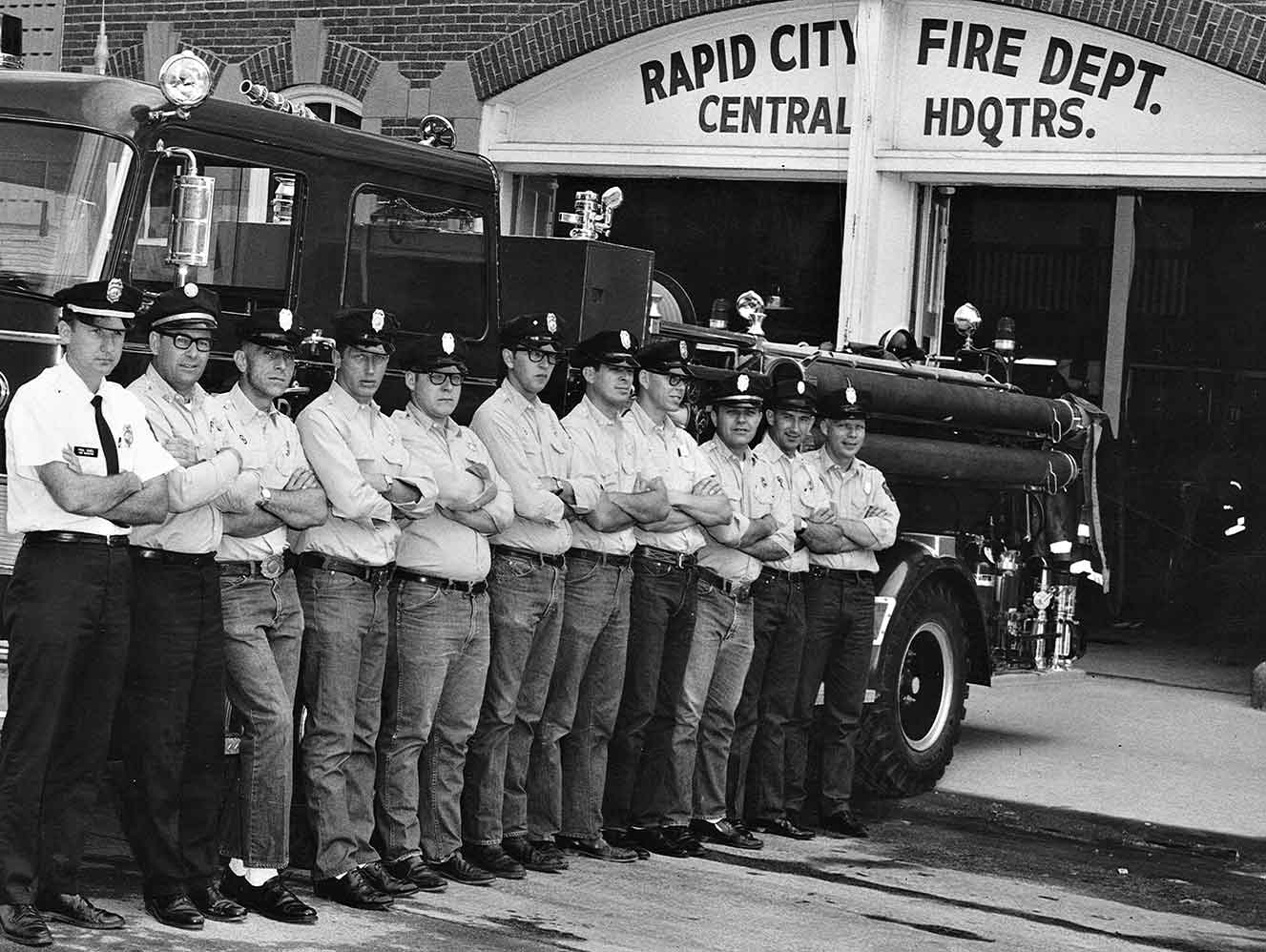 11 firemen stand outside of Rapid City's central headquarers